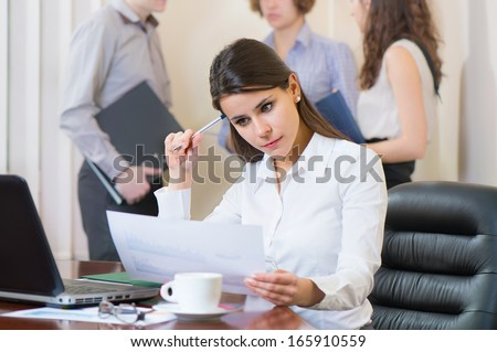 Portrait of businesswoman with laptop and documents in office