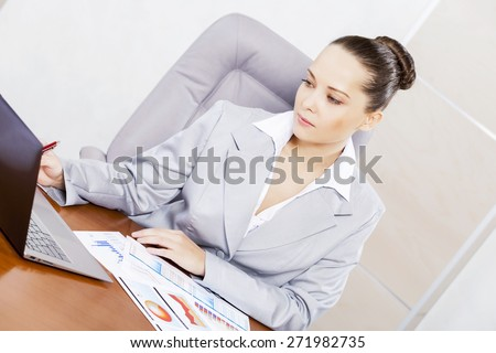 Portrait of businesswoman with laptop working at her office