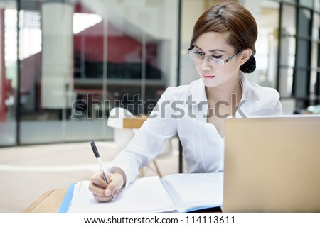 Portrait of businesswoman with laptop writes on a document at her office - stock photo