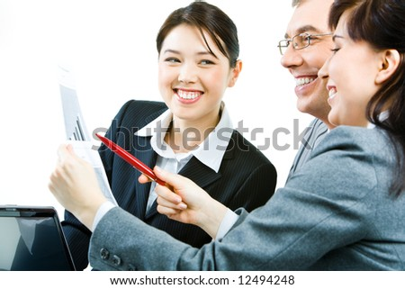 Portrait of businesswoman with paper in hands and pointing at the document while her colleague looking at it