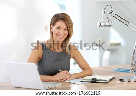 Portrait of businesswoman working on laptop - stock photo
