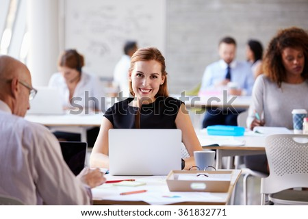 Portrait Of Businesswoman Working On Laptop In Busy Office
