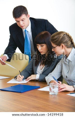Portrait of businesswoman writing on the document with two colleagues near by - stock photo