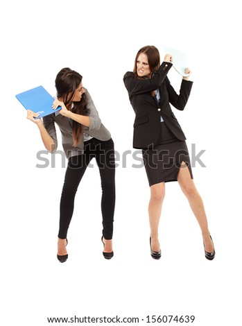 Portrait of businesswomen beating each other with notebooks isolated on white - stock photo