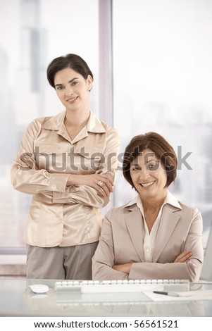 Portrait of businesswomen in office, smiling at camera.