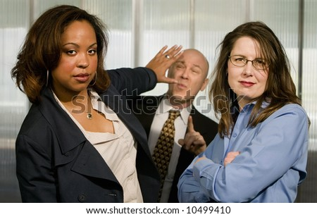 Portrait of Businesswomen Pushing back a Businessman - stock photo