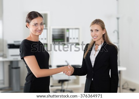 Portrait of businesswomen shaking hands while standing in office - stock photo