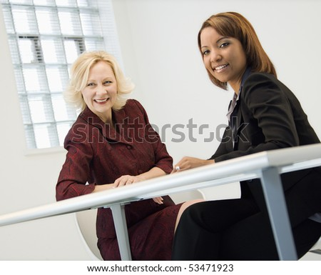 Portrait of businesswomen sitting at office desk smiling. - stock photo