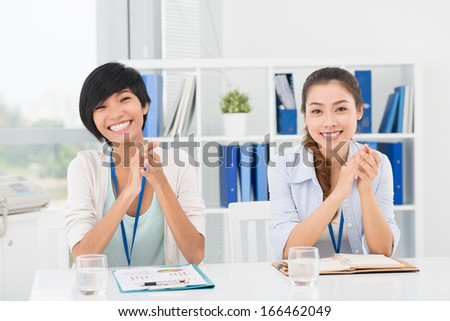 Portrait of businesswomen sitting at the seminar and posing at camera - stock photo