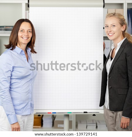 Portrait of businesswomen standing near flip chart in office - stock photo