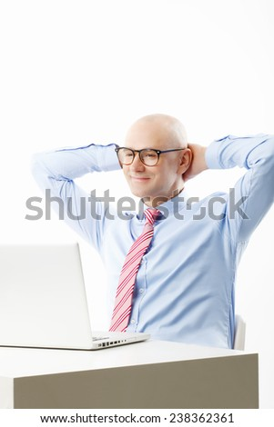 Portrait of busy businessman sitting in front of computer while raising his hand. Isolated on white background.  - stock photo