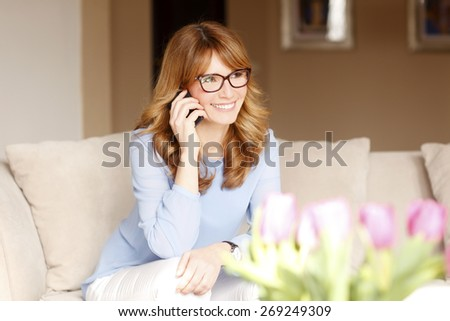 Portrait of busy businesswoman making telephone conversation while sitting and working at home. Home office.  - stock photo