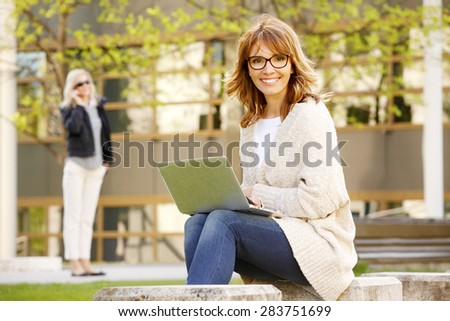 Portrait of busy businesswoman sitting at business park while using private banking on laptop.  - stock photo