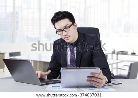 Portrait of busy caucasian businessman using laptop computer and a digital tablet in the office - stock photo