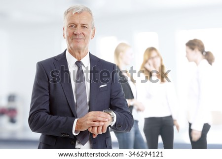 Portrait of busy sales man checking the time while business people consulting at background.
