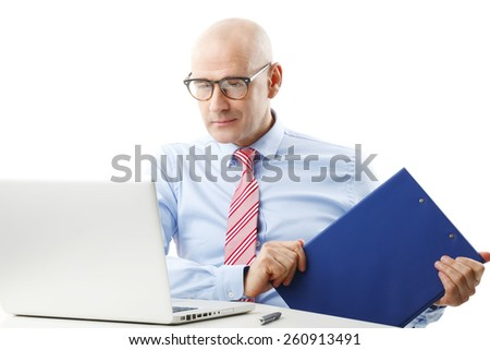 Portrait of busy sales man sitting at desk in front of laptop while holding file in his hand. Isolated on white background.  - stock photo