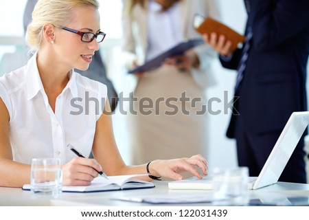 Portrait of busy secretary looking at laptop while networking - stock photo
