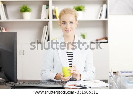Portrait of busy young financial assistant sitting at her workplace and drinking a cup of tea while working on computer.