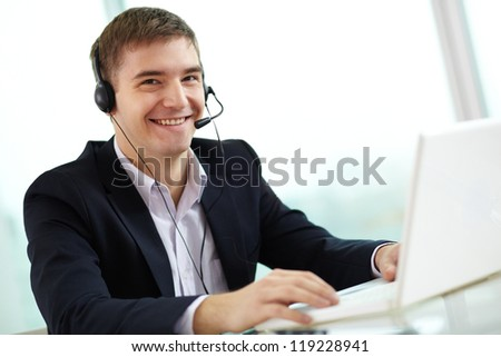 Portrait of busy young man in headset looking at camera while typing - stock photo