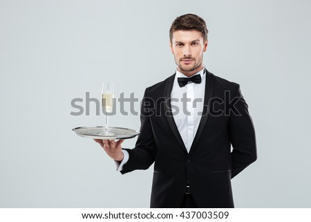 Portrait of butler in tuxedo and bow tie holding tray with glass of champagne over white background