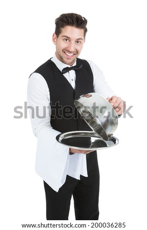 Portrait of butler lifting cloche from serving tray over white background - stock photo