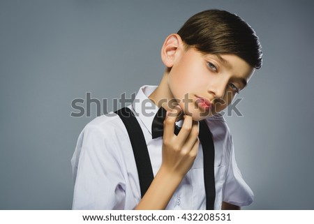 Portrait of calm and mistrust boy isolated on gray background. Normal human emotion, facial expression. Closeup - stock photo