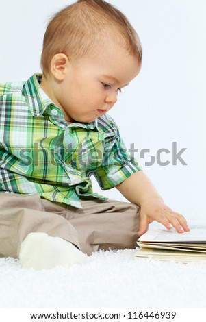 Portrait of calm boy touching page of open book over white background