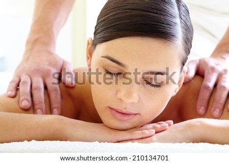 Portrait of calm female enjoying luxurious procedure of massage - stock photo