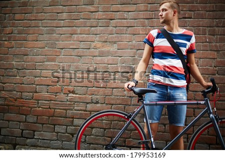 Portrait of calm guy with bicycle standing against brick wall - stock photo