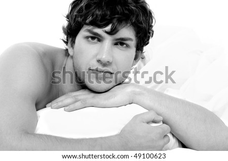 Portrait of calm man with a handsome face lying in bed with pillow - stock photo