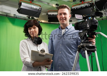 Portrait Of Cameraman And Floor Manager In Television Studio - stock photo