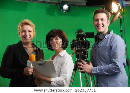 Portrait Of Cameraman With Presenter And Floor Manager In Television Studio - stock photo