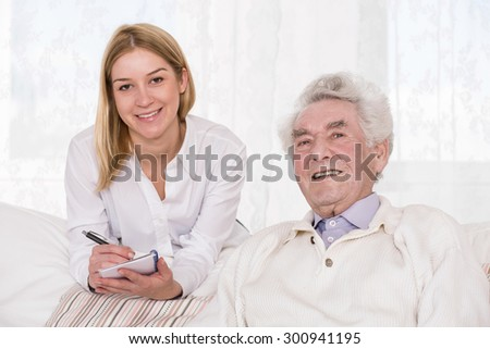 Portrait of care assistant and elder man - stock photo