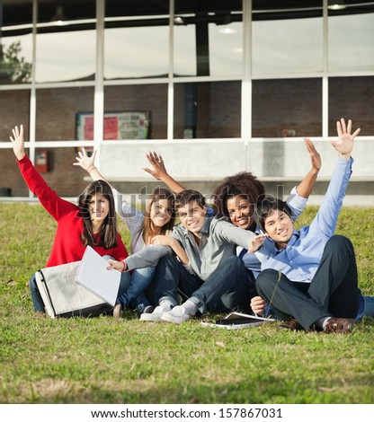Portrait of carefree college students with hands raised sitting on grass at campus - stock photo