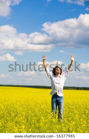 Portrait of carefree young man standing on field with raised arms and enjoying summer day