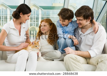Portrait of careful parents and their two children enjoying weekend day at home - stock photo