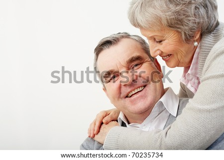 Portrait of careful wife embracing her husband over white background