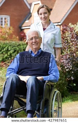 Portrait Of Carer Pushing Senior Man In Wheelchair - stock photo