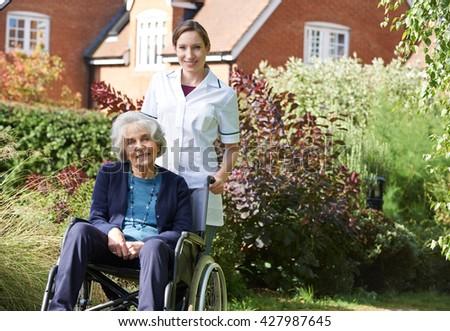 Portrait Of Carer Pushing Senior Woman In Wheelchair - stock photo