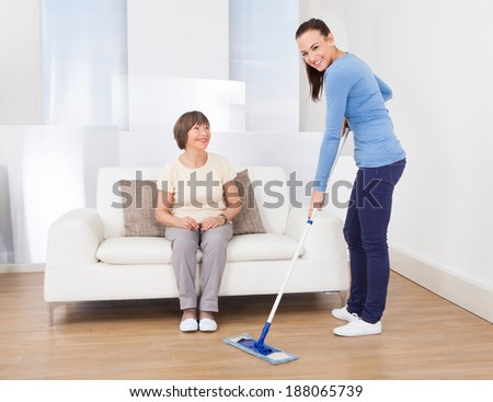 Portrait of caretaker cleaning floor with mop while senior woman sitting on sofa at nursing home
