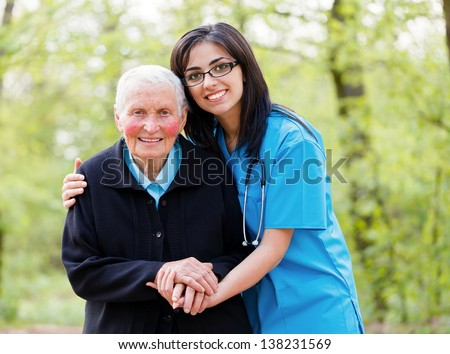 Portrait of caring nurse helping elderly lady holding her hands. - stock photo