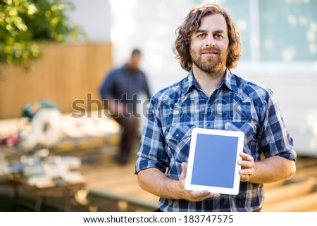 Portrait of carpenter displaying tablet computer with coworker working in background at construction site - stock photo