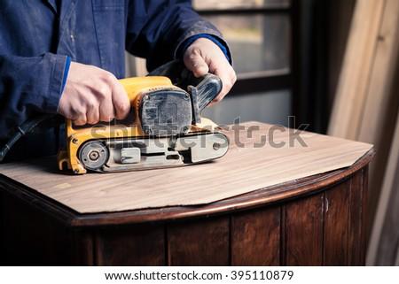Portrait of Carpenter restoring old wooden furniture with belt sander in his Wood Shop - stock photo