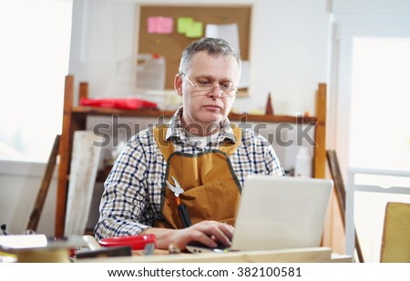 Portrait of carpenter sitting at his workshop and working with laptop  Small business. - stock photo