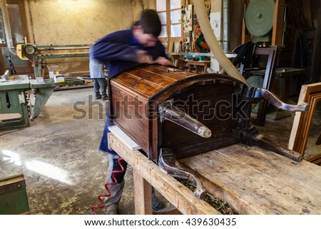 Portrait of Carpenter wearing Blue Overalls restoring Wooden Furniture in his workshop. Blurred subject. - stock photo