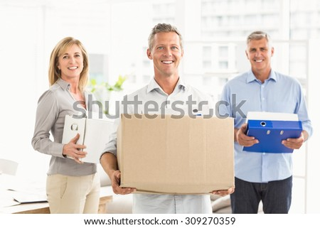 Portrait of casual business people carrying cartons in the office