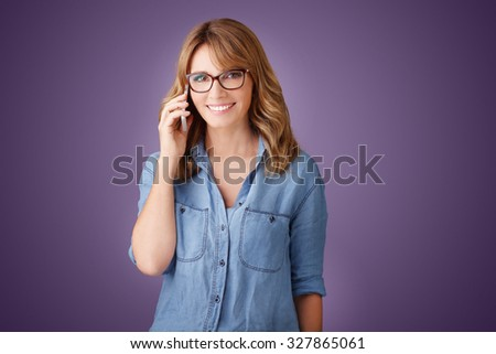 Portrait of casual business woman holding in her hand a mobile phone and making call while standing at isolated background.  - stock photo