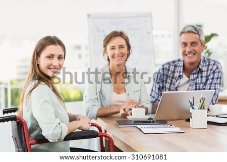 Portrait of casual businesswoman in wheelchair with colleagues in the office - stock photo