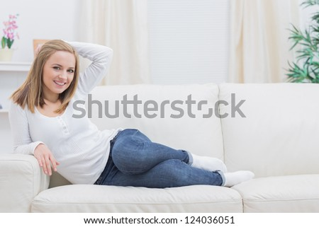 Portrait of casual happy young woman sitting on sofa at home
