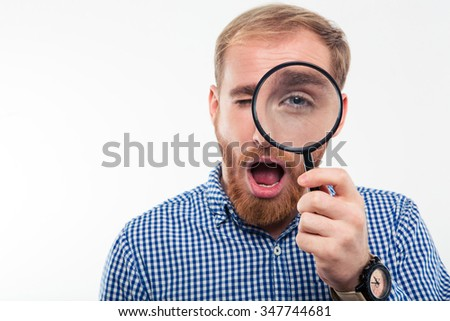 Portrait of casual man looking through magnifying glass at camera isolated on a white background